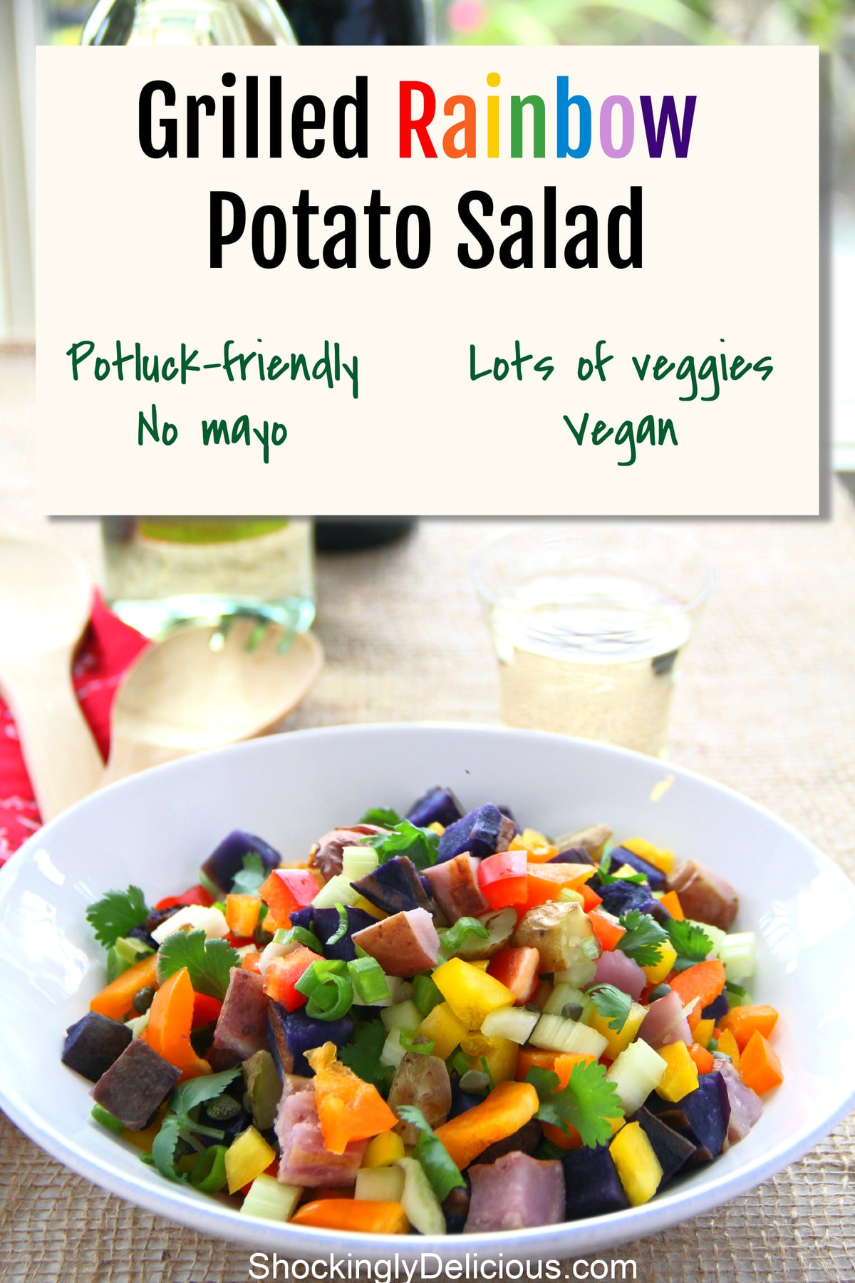 Grilled Rainbow Potato Salad in a white bowl on a burlap map with a wine glass behind it and the recipe title above it