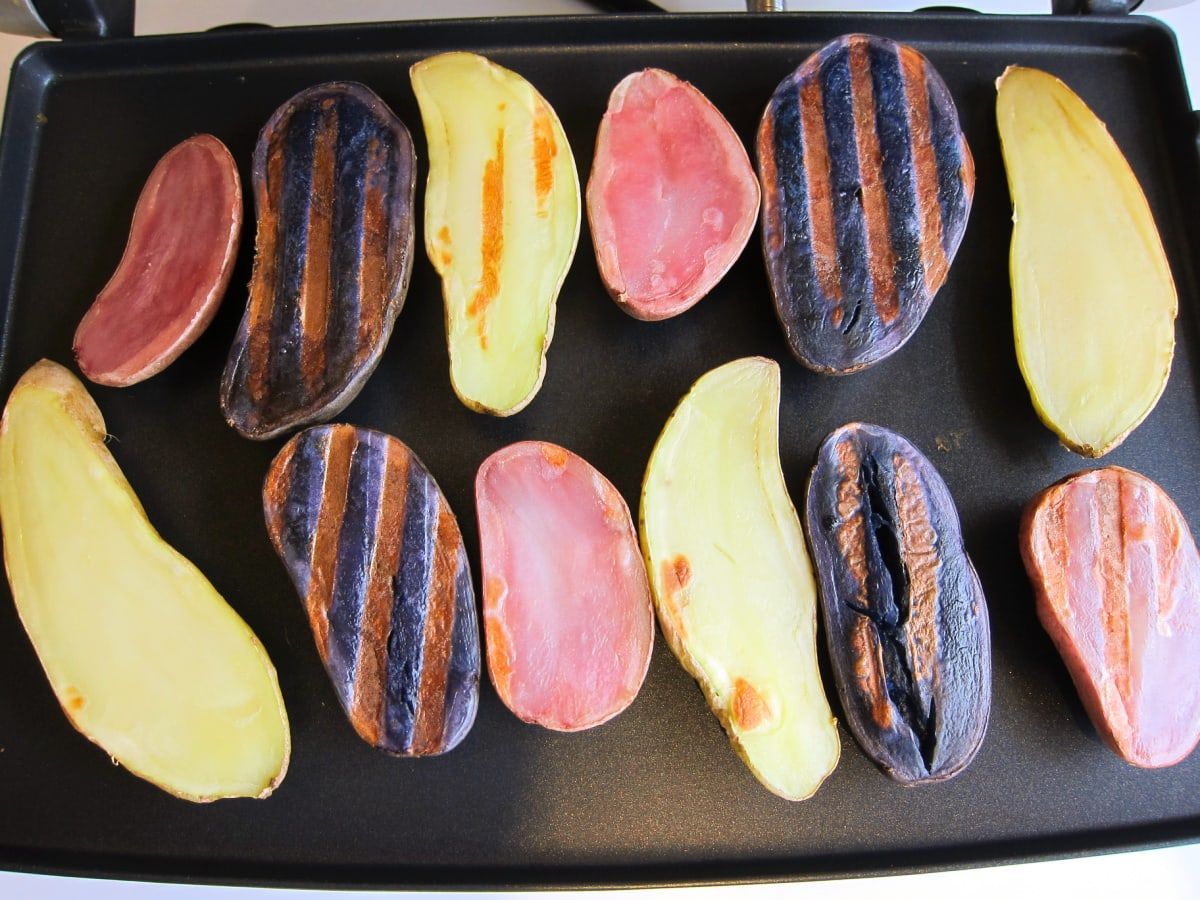 Purple, red and white fingerling potatoes on a black panini grill with grill marks on them