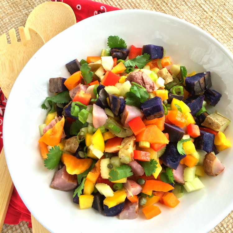 Grilled Rainbow Potato Salad in a white bowl with a bandana for a napkin and burlap for table covering