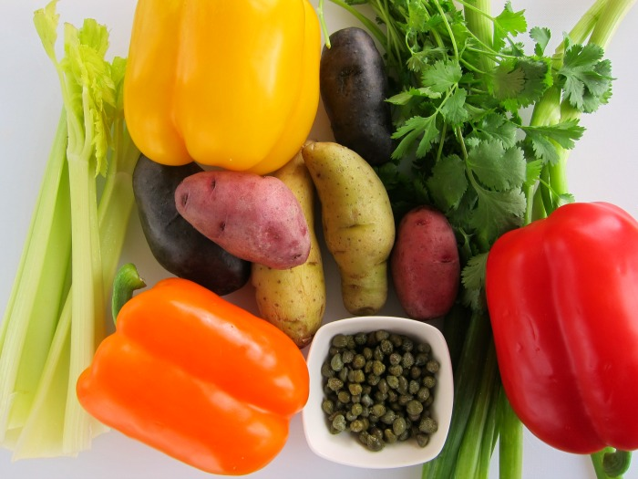 Ingredients for Grilled Rainbow Potato Salad on a white board -- celery, potatoes, bell peppers, cilantro, onion and capers
