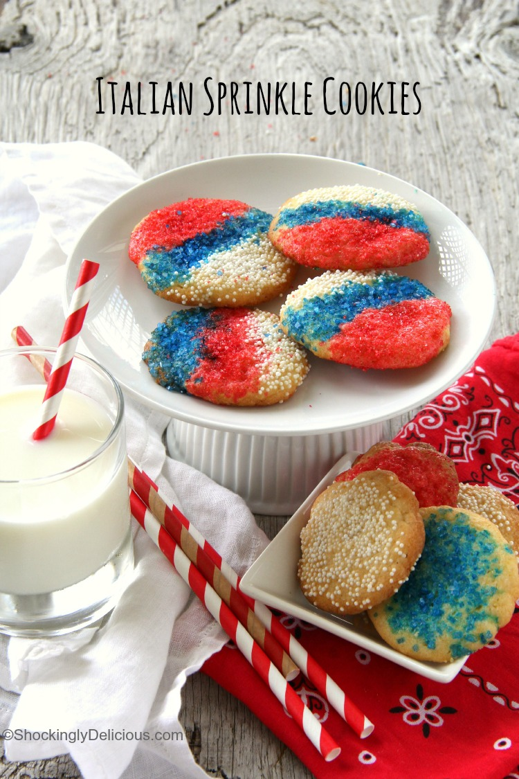 4 Italian Sprinkle Cookies with red white and blue sprinkles on an elevated white cake stand with a glass of milk to the sidedings, easy recipe | ShockinglyDelicious.com