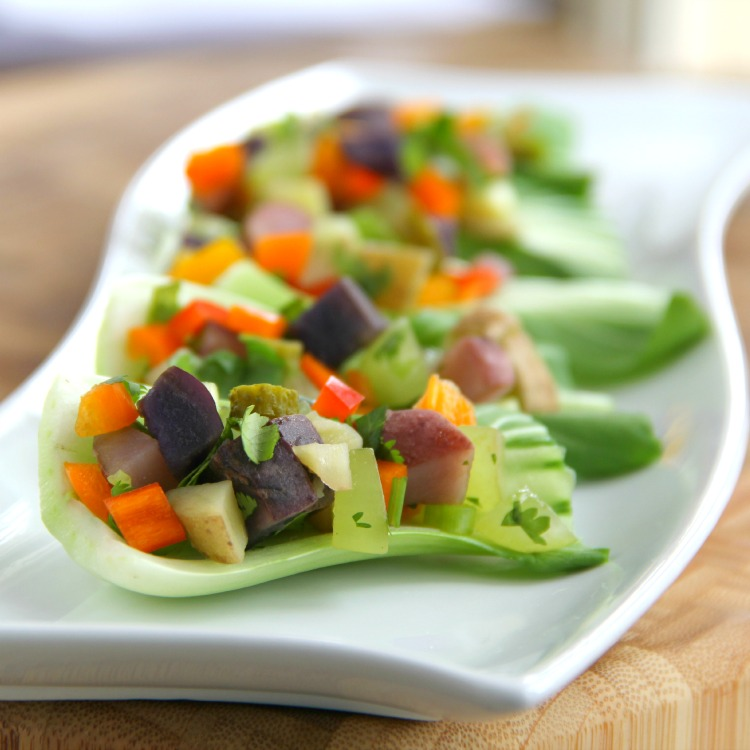 Potato Salad in baby bok choy cups on a white curvy serving plate