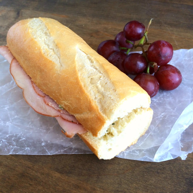 French Ham and Butter Sandwich on a baguette with grapes alongside