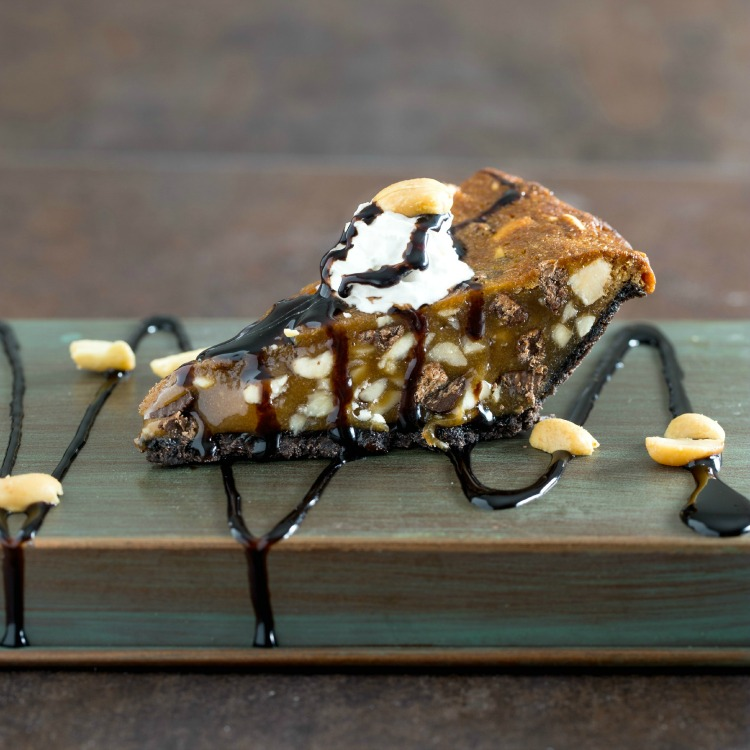 Wedge of Chocolate Chip Peanut Pie with chocolate sauce on top