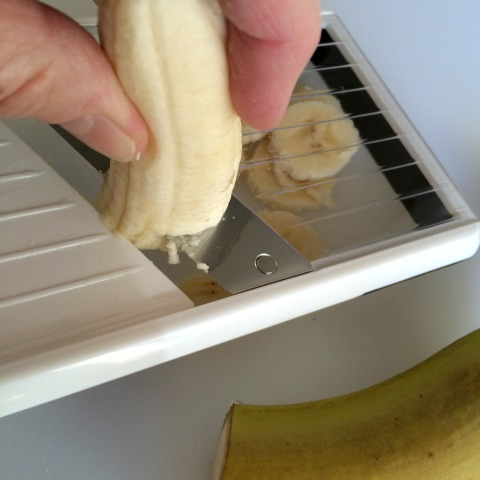 Slicing the bananas for the Barley Banana Berry Breakfast Bowl on ShockinglyDelicious.com