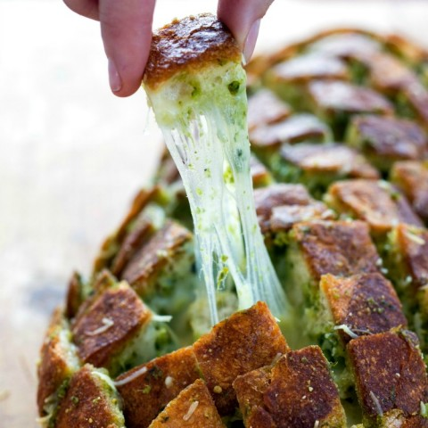Cheesy Pull-Apart Pesto Bread: People will go crazy for this Cheesy Pull-Apart Pesto Bread that's like garlic knots gone wild. Cross cutting the bread makes the loaf easy to pull apart. | ShockinglyDelicious.com
