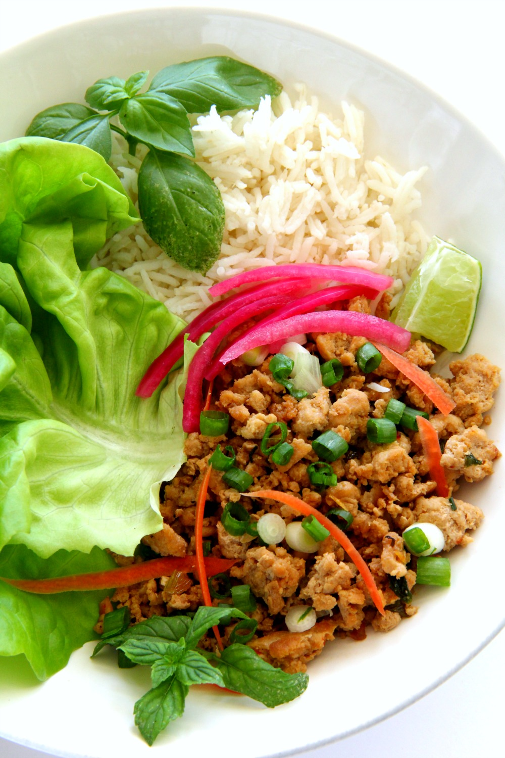 thai turkey rice bowl in a white bowl on a white counter with bright vegetables on top