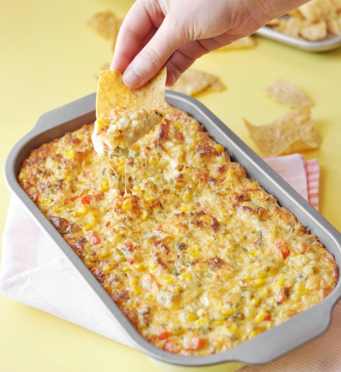 spicy-corn-dip-by-rachel-hollis in a gray baking dish against a yellow background