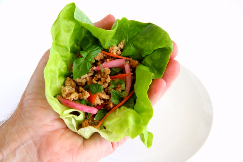 Thai Turkey Lettuce Wraps feature ground turkey flavored with fish sauce, soy sauce and lime juice, freshened with herbs and stuffed into a lettuce leaf for a low-carb meal.  Serve it as a rice bowl for a heartier dinner.