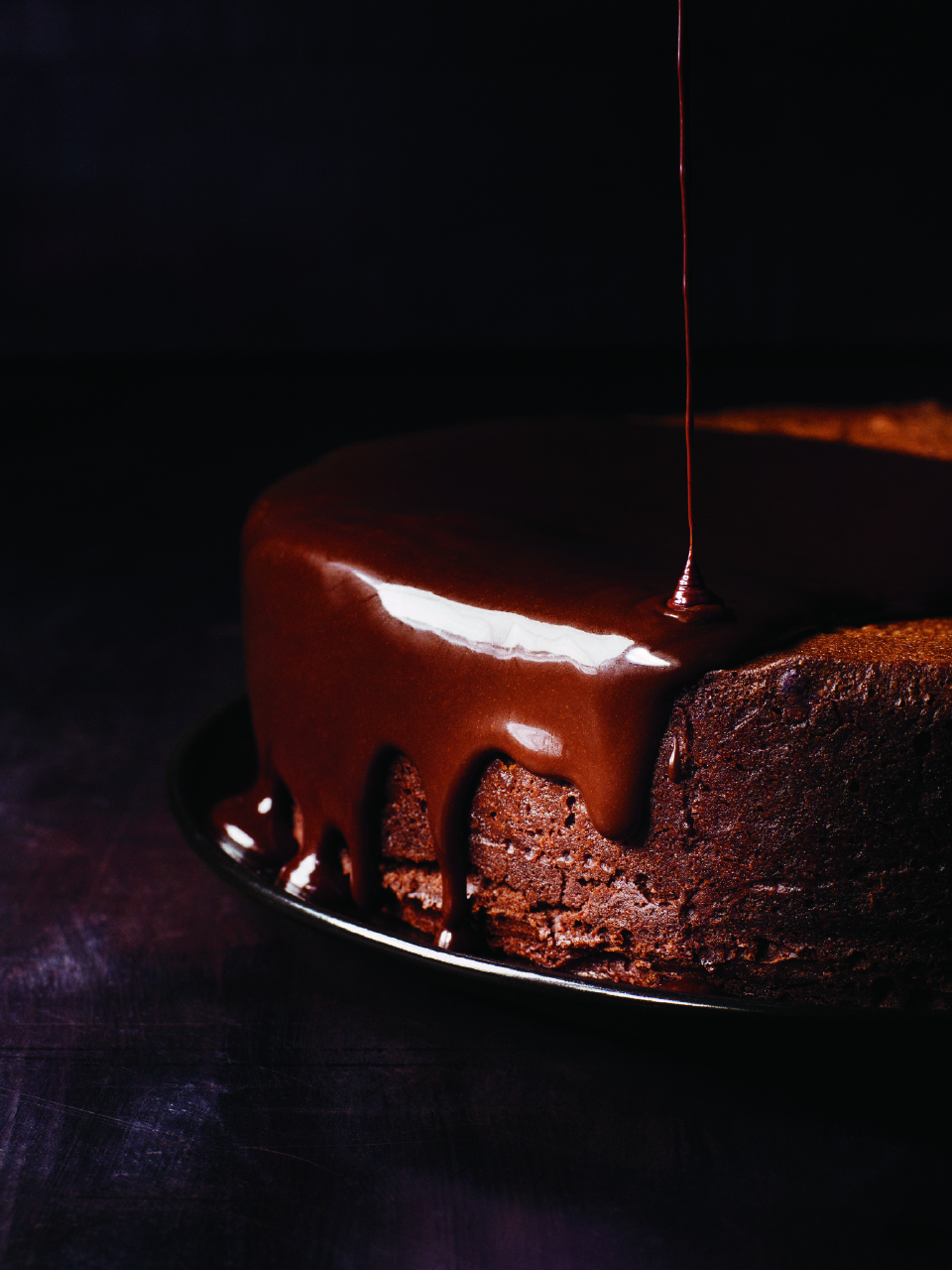 darkest-chocolate-cake-with-red-wine-glaze against a dark background