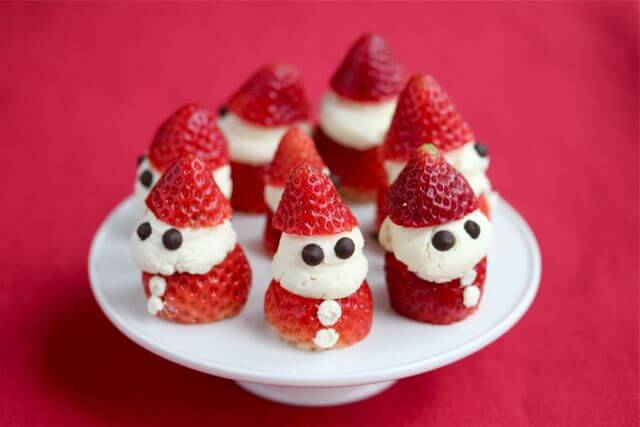 santa-shaped strawberries on a white cake plate with a red background