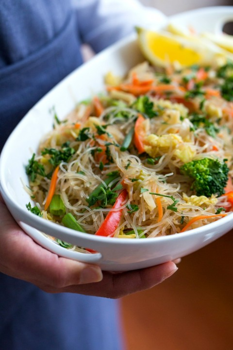 Stir-Fried Cellophane Noodles (vegan pancit) in a white bowl, held by a person in a blue apron