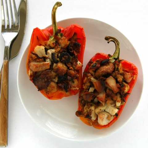 Striped Enjoya peppers stuffed with leftover Thanksgiving turkey and stuffing on a white plate against a white background.