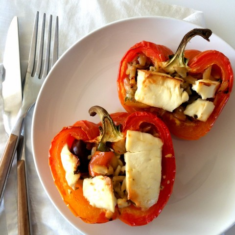 2 Enjoya striped peppers stuffed with Mediterranean orzo salad topped with feta on a white plate
