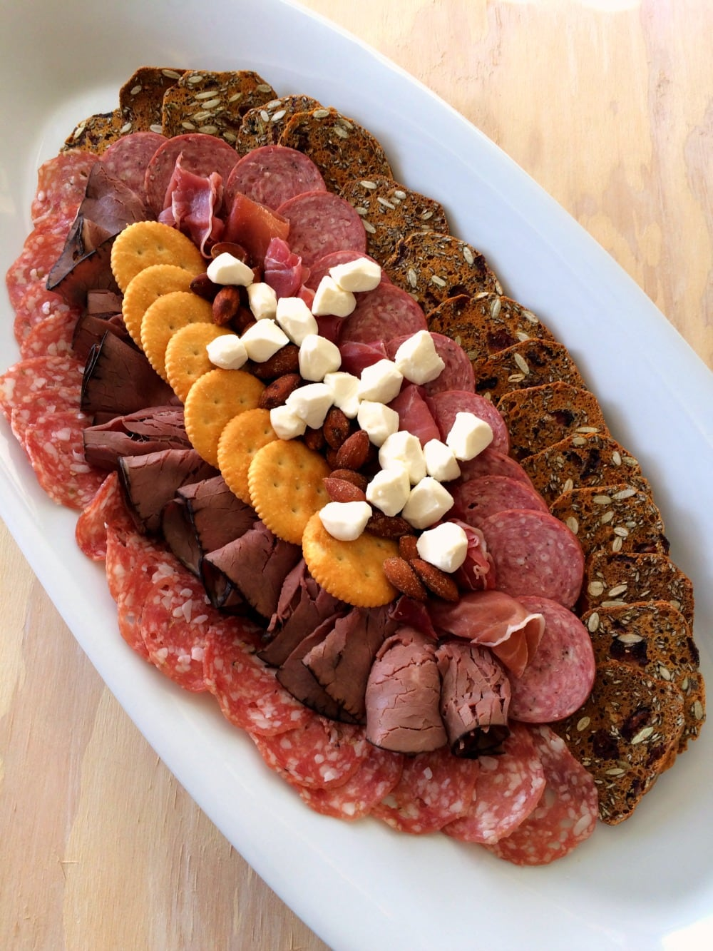 Meat and cheese arranged in the shape of a football on a white oval platter