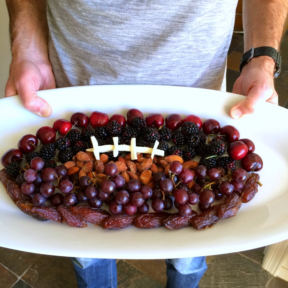 Man holding a Fruit Football on a white platter on ShockinglyDelicious.com