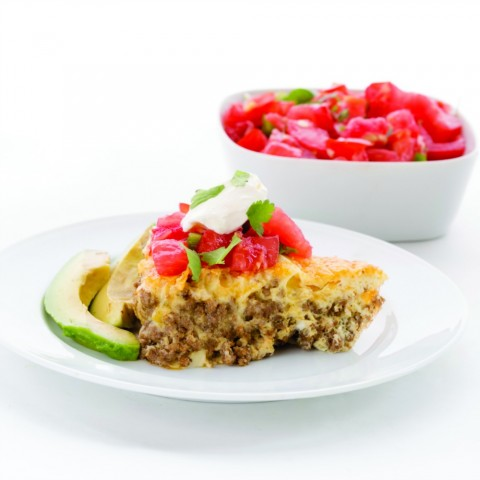 Easy Taco Pie on a white plate with pico de gallo on top and in a bowl behind it