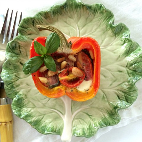 Striped bell peppers stuffed with caprese ingredients on a green ceramic lettuce plate with bambook silverware beside it.  Stuffed Pepper on ShockinglyDelicious.com