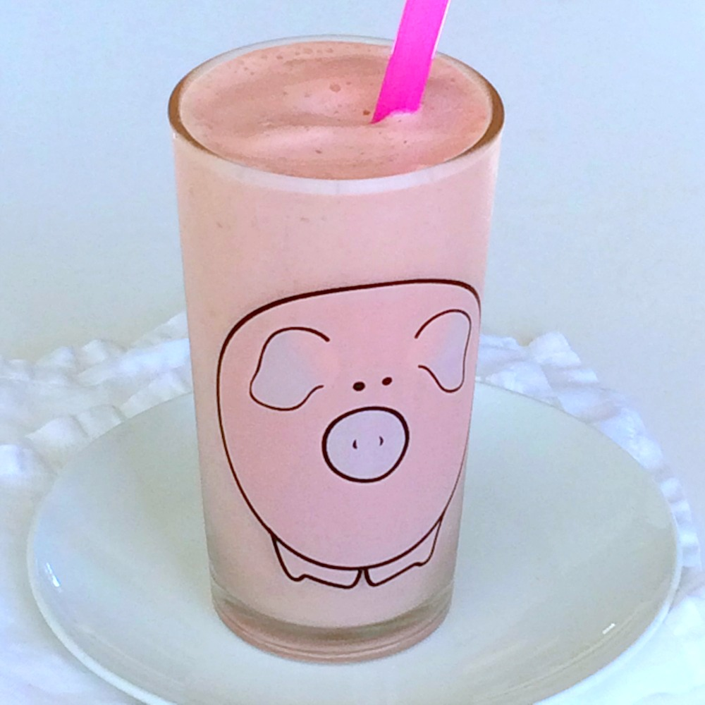 Pineapple Blood Orange Smoothie recipe in a glass decorated with a pink pig
