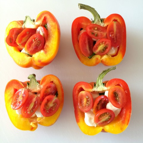 Striped Enjoya peppers cut in half with grape tomatoes inside