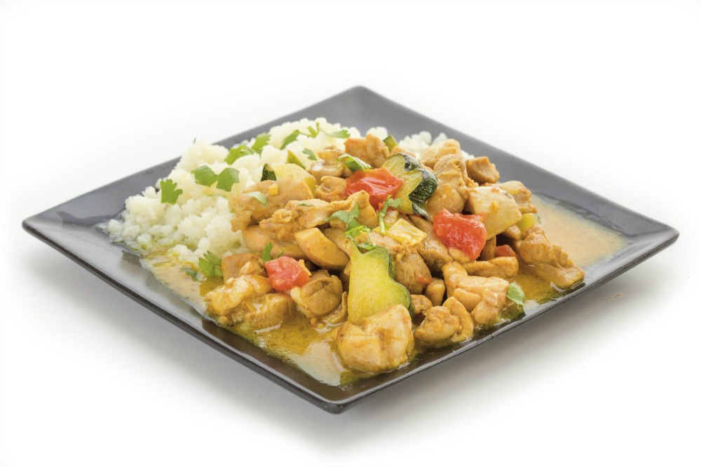 Chicken Coconut Curry on rice on a black plate