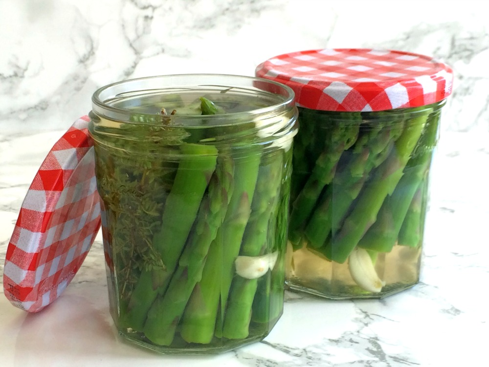 2 jars of Refrigerator Pickled Asparagus on a white marble background on ShockinglyDelicious.com