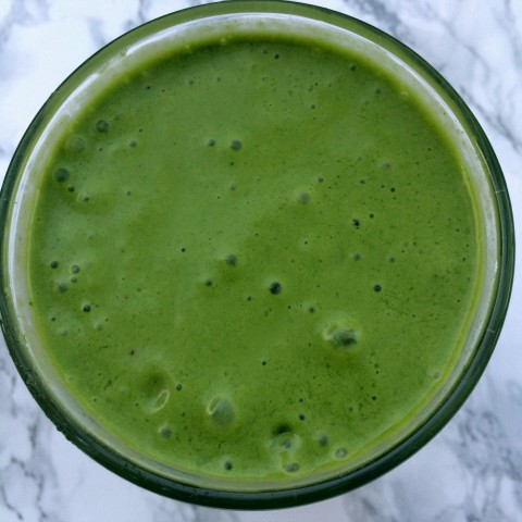 Teenage Boy Protein Smoothie -- green spinach banana smoothie in a glass on a marble background