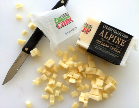 Chop the cheese for Kale Salad with Apples, Carrots, Cheese and Capers
