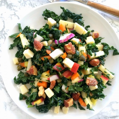 Kale Salad with Apples, Carrots, Cheese and Capers on a white plate and marble background on ShockinglyDelicious.com