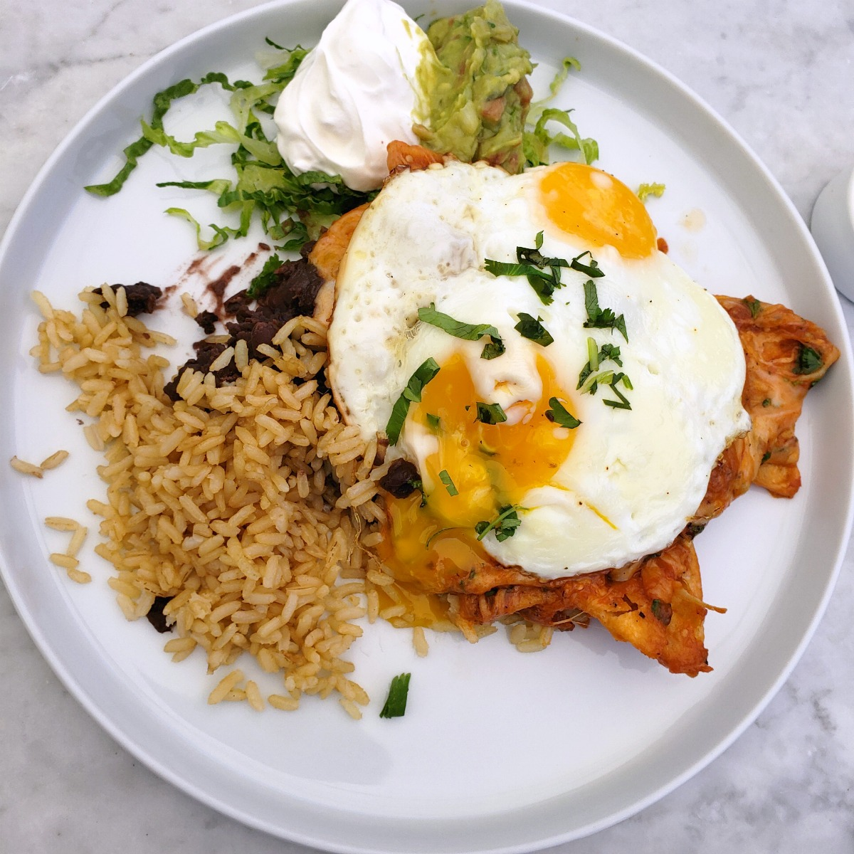 Chilaquiles with fried eggs on top, rice and guacamole alongside on a white plate at The Sparrow Cafe in Malibu