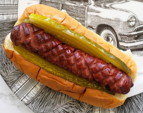 Crosshatch cut on a hot dog in a bun on a decorated plate