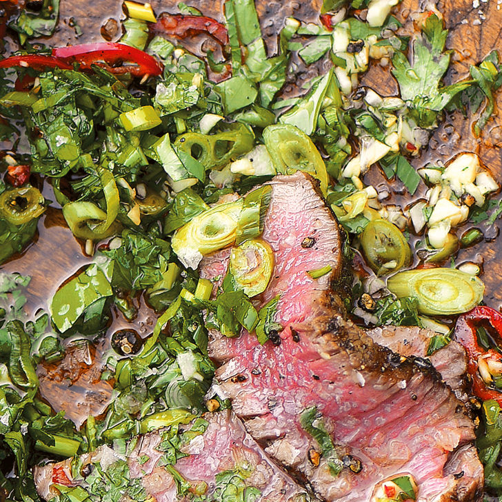 Filet mignon slices mingle with herbs on a wooden board for Cutting Board Sauce