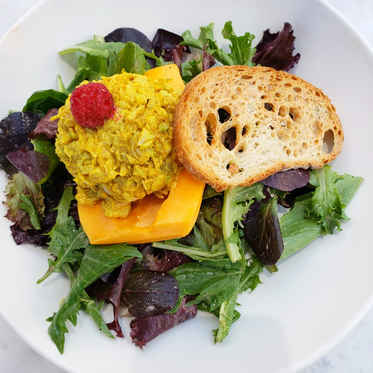 Papaya Curried Chicken Salad atop mixed greens in a white bowl at The Sparrow Cafe in Malibu