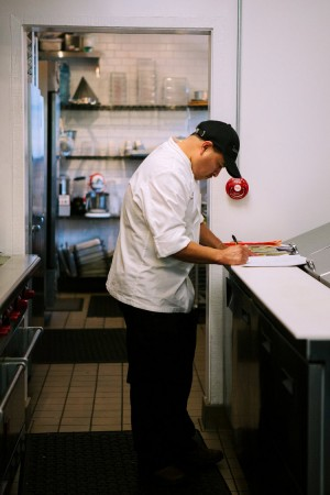 Chef Victor Rosales working on a clipboard in the kitchen at The Sparrow Club Malibu