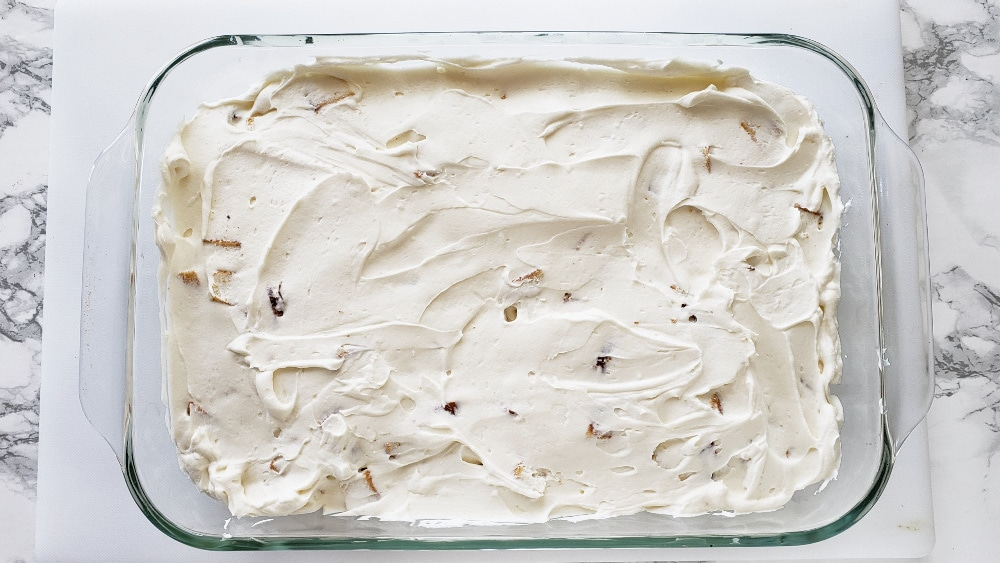 Whipped cream layer completely covers the cake layer in a glass dish on a white boardes on ShockinglyDelicious.com