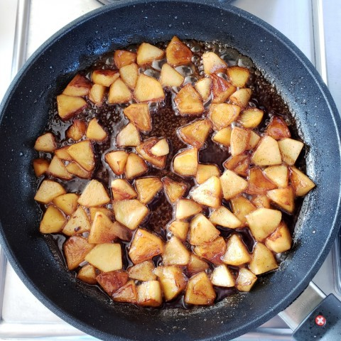 Apples, maple syrup and cinnamon sauce in skillet