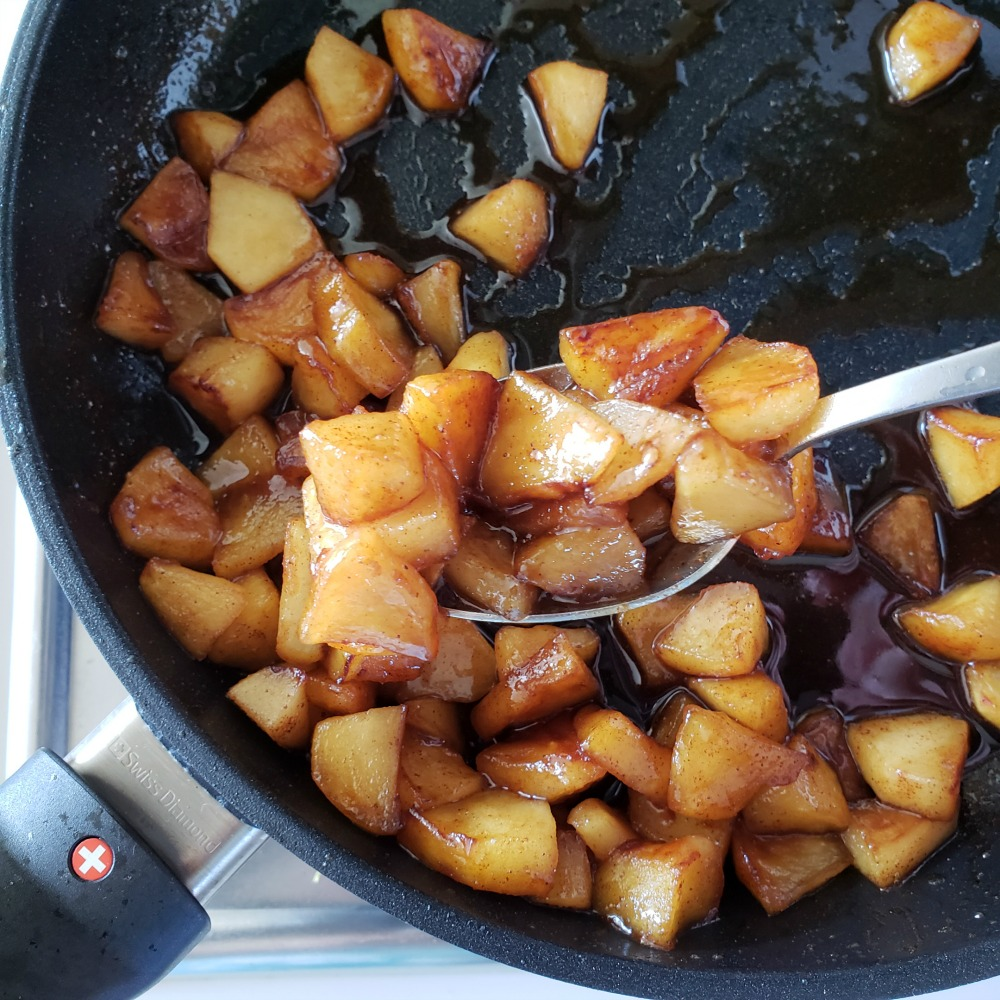 Spoon lifting caramelized apples in cinnamon maple syrup in the black skillet