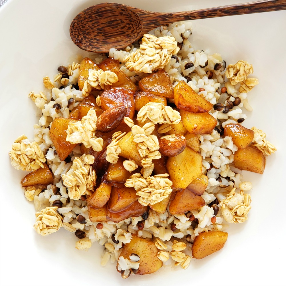 Apple Crisp Breakfast Bowl has apples, oatmeal and granola heaped in a white bowl with a wooden spoon at the top