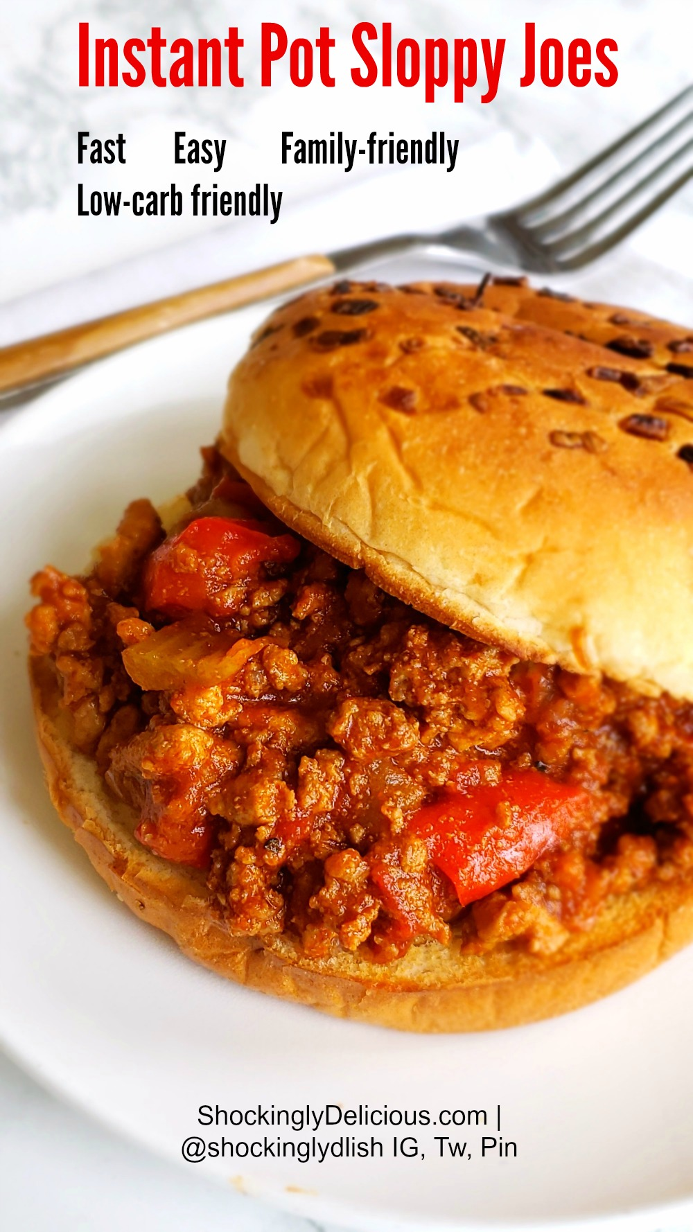 Instant Pot Sloppy Joes on a bun on a white plate with fork alongside