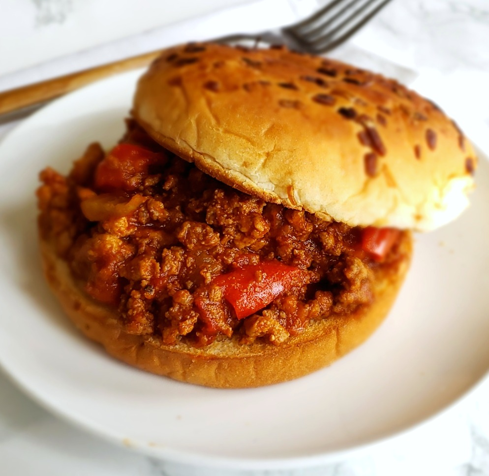 Simple Instant Pot Sloppy Joes on a bun on a white plate on ShockinglyDelicious.com