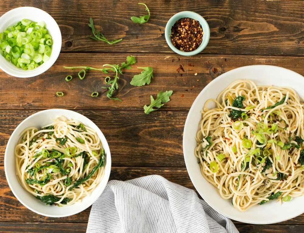 Green Pasta Puttanesca in two white bowls, chopped green onions and crushed red pepper in other bowls, on a wooden table