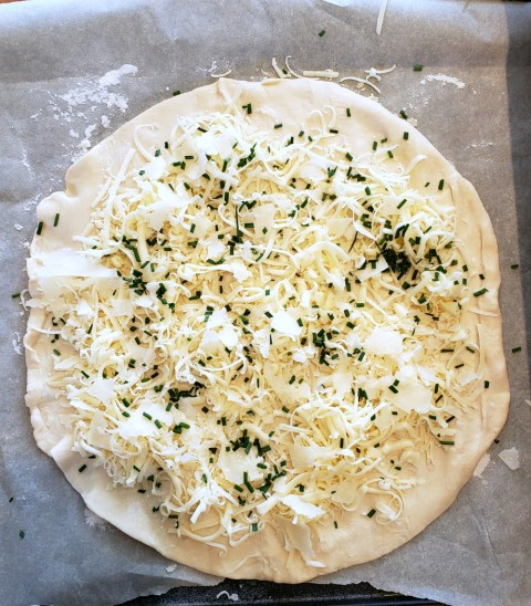 Puff pastry round with cheeses and chives for Cheesy Fondue Spirals on ShockinglyDelicious.com