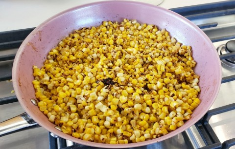 Corn toasting in the skillet for Esquites on ShockinglyDelicious.com