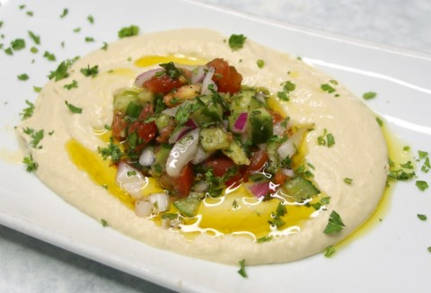 Hummus garbanzo dip on a white plate with parsley on top on ShockinglyDelicious.com