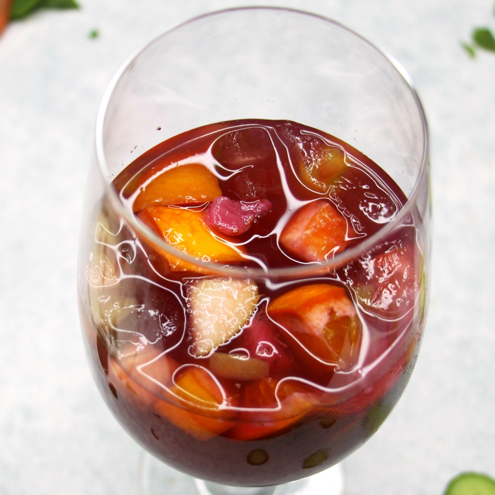 Merlot Sangria in a glass with fruit floating on top against a white background