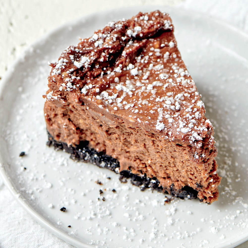 Wedge of Double Chocolate Fudge Cheesecake with powdered sugar on top