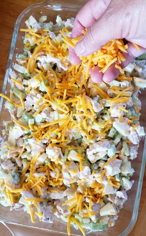 Sprinkle Cheddar Cheese on the Hot Chicken Salad on ShockinglyDelicious.com
