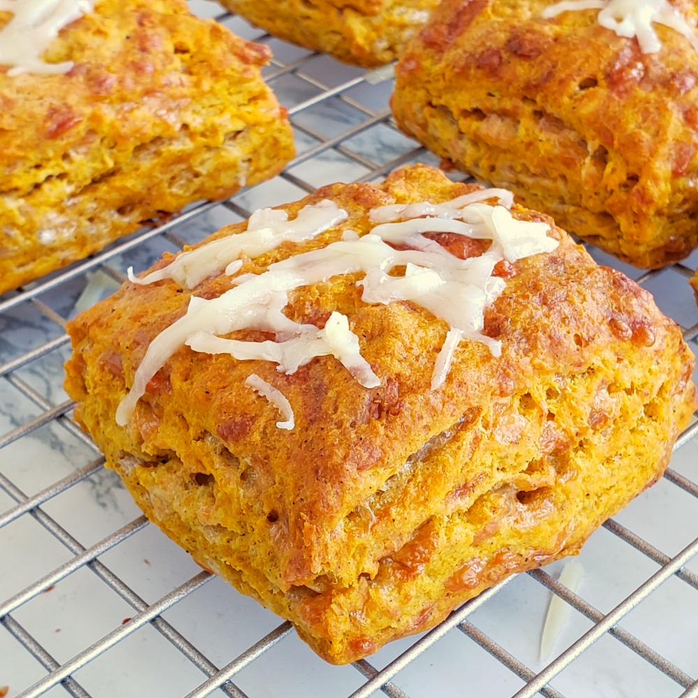 Pumpkin Cheddar Biscuits on a cooling rack with cheese shreds on top of the biscuits