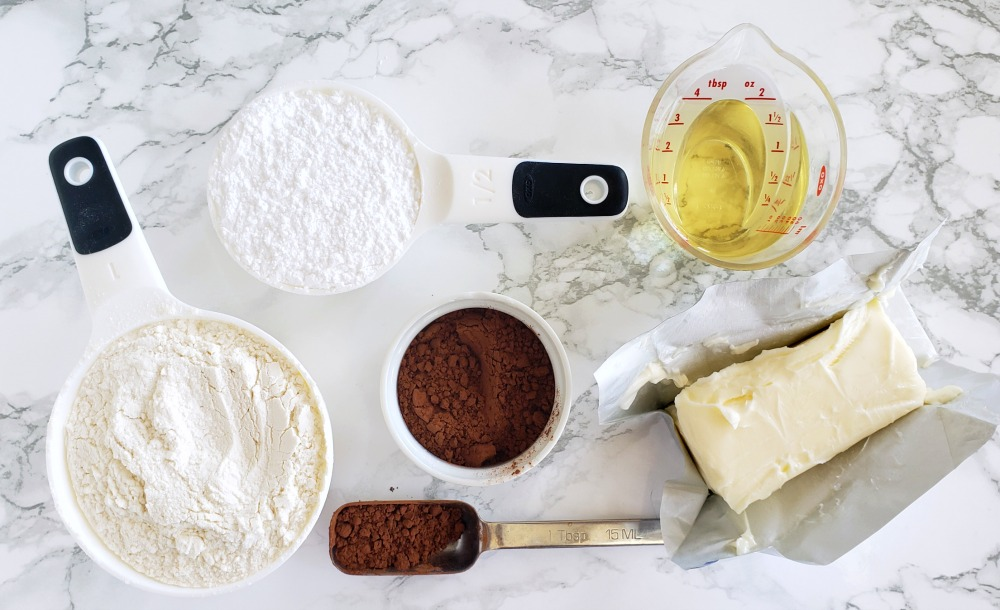 Ingredients for Rich Chocolate Shortbread Cookies on a white marble counter on ShockinglyDelicious.com
