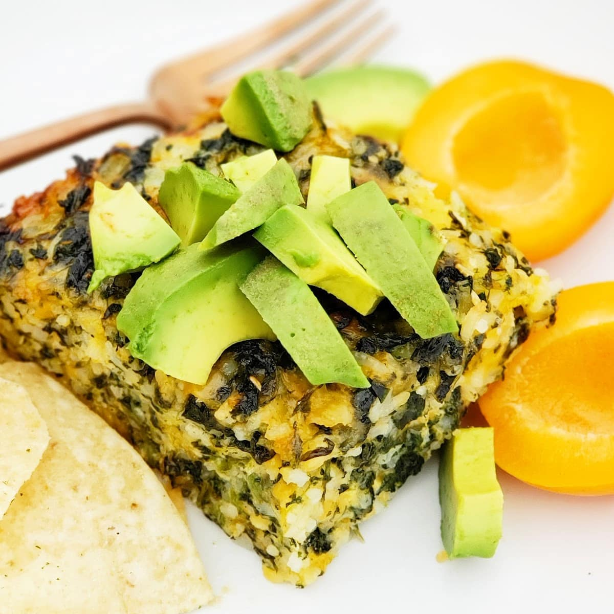 Spinach Rice Casserole topped with chopped avocado with corn chips and apricot on the side